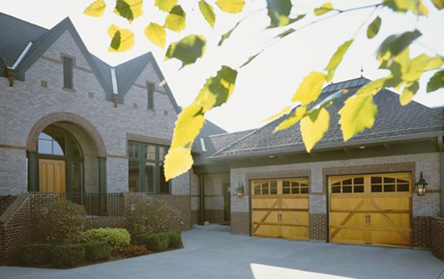 Insulated Carriage-Style Garage Doors with Leaves in Foreground