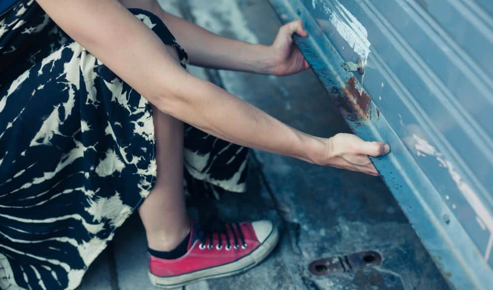 Woman in Dress and Pink Chuck Taylor Shoes Manually Opening Garage Door